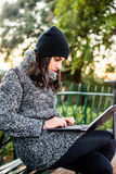 Beautiful girl researching on her tablet in a park - close up. Young girl sitting on a bench with a grey coat and black hat and researching something on her Stock Image