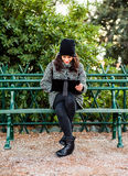 Beautiful girl researching on her tablet in a park - front view. Young girl sitting on a bench with a grey coat and black hat and researching something on her Royalty Free Stock Photo