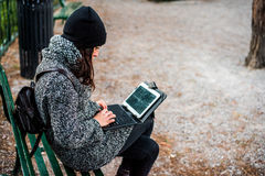 Beautiful girl researching on her tablet in a park. Young girl sitting on a bench with a grey coat and black hat and researching something on her tablet royalty free stock image
