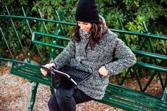Beautiful girl researching and smiling with tablet in a park. Young girl sitting on a bench with a grey coat and black hat and researching something on her royalty free stock images