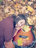 Beautiful girl resting on autumn leafs. With guitar stock image
