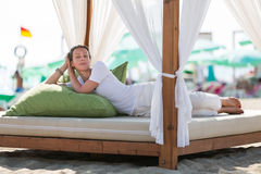 Beautiful girl resting on beach in a bed Royalty Free Stock Photos