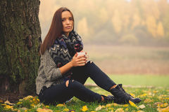 Beautiful girl resting and drinking coffee sitting in autumn garden Stock Images