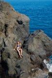 Beautiful girl resting in natural ocean swimming pool Stock Photos