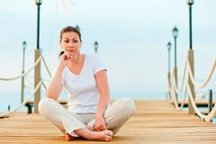 Beautiful girl resting on a pier Royalty Free Stock Image