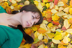 Beautiful girl  resting on yellow autumn leaves Royalty Free Stock Images