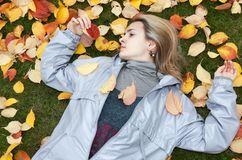 Beautiful girl rests upon autumn sheet Stock Image
