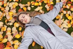 Beautiful girl rests upon autumn sheet Stock Photos