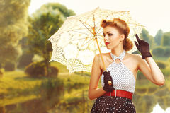 Beautiful girl in retro dress with retro umbrella. Near the pond Royalty Free Stock Photos
