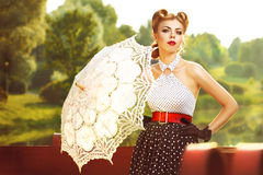 Beautiful girl in retro dress with retro umbrella. Near the pond Royalty Free Stock Images