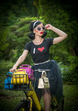 Beautiful girl with retro look wearing a black outfit having fun in park with bicycle. Outdoor lifestyle concept. Vintage scenery. Stock Photo