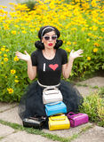 Beautiful girl with retro look wearing a black outfit having fun in park displaying a lot of colored bags. Fashionable brunette Stock Image