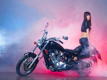 Beautiful girl on a retro motorcycle. In smoke cloud Royalty Free Stock Photos