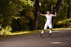 Beautiful girl rides roller skates in park Royalty Free Stock Images