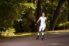 Beautiful girl rides roller skates in park Stock Images