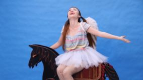 Beautiful girl rides a toy horse. HD stock video footage