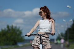 Beautiful girl riding a bicycle. Pretty young woman in sunglasses enjoying the warm summer weather, resting on the wheel of bicycle and looking away from the Royalty Free Stock Image