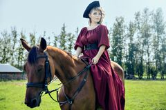 Beautiful girl riding a brown horse. Beautiful girl in a red long red dress and in a black hat with a cocked hat riding a brown horse royalty free stock images