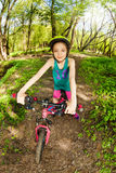 Beautiful girl riding her bike on the forest trail Stock Photo