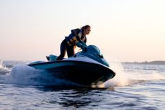 Beautiful girl riding her jet skis Royalty Free Stock Image