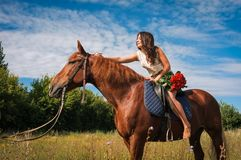 Beautiful girl riding a horse against blue sky Stock Photography