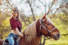Beautiful girl riding horse on autumn field Stock Photo