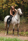 Beautiful girl riding a horse without bridle or saddle Royalty Free Stock Image