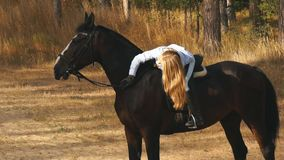 Beautiful girl riding on a horse hugging her and stroking stock video footage