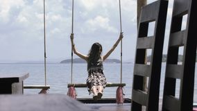 Beautiful girl is riding on a swing against the sea in a cafe on the pier. Dress, long hair, swing on the rope stock video