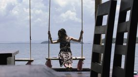 Beautiful girl is riding on a swing against the sea in a cafe on the pier. stock video