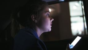 Beautiful girl riding in a taxi at night sitting on the backseat and holding her phone. She is worried, trying to find. Something and asks a driver about stock footage