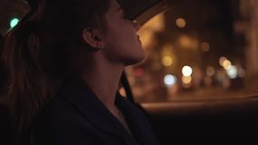 Beautiful girl riding in a taxi at night sitting on the backseat and moving her head listening to the music. Happy woman. In taxi. Night live. Slowmotion shot stock video footage