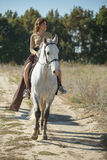 Beautiful girl riding on the white horse in a Stock Images