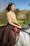 Beautiful girl riding a white horse Stock Image