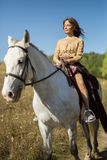 Beautiful girl riding a white horse Royalty Free Stock Images