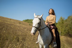 Beautiful girl riding a white horse Stock Images