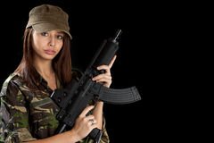 Beautiful girl with a rifle. Beautiful woman in action pose, isolated on black Royalty Free Stock Photography