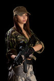 Beautiful girl with a rifle. Beautiful girl in action pose, isolated on black Stock Images