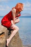 Beautiful girl on the rock. Beautiful girl sitting on the rock in the Crimea (Ukraine, Novyi Svet Stock Images