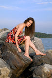 Beautiful girl on rock near sea Royalty Free Stock Photography