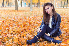 Beautiful girl in rock style with bright makeup in white jacket and black pants and boots in a leather jacket sitting in the Park Royalty Free Stock Photos