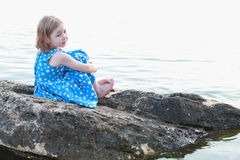 Beautiful girl on a rock between waters Stock Images