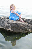 Beautiful girl on a rock between waters Royalty Free Stock Images