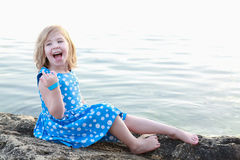 Beautiful girl on a rock between waters Royalty Free Stock Image