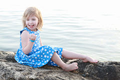 Beautiful girl on a rock between waters Stock Photos