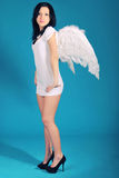It is a beautiful girl in a role of angel on a blu Royalty Free Stock Images