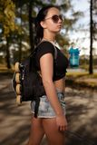 Beautiful girl with roller skates in backpack drinks water Royalty Free Stock Image