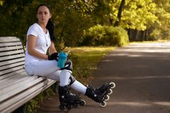 Beautiful girl on roller skates in park sits on bench and drinks water Stock Photos