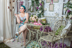 Beautiful girl in the room with flowers. Bright young lady sitting in the room with flowers Royalty Free Stock Photography