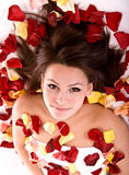 Beautiful girl in rose petal. Beautiful happy girl in rose petal. Spa beautician Royalty Free Stock Photography